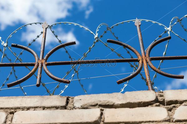 Фотография на тему Колючая проволока на заборе на фоне ярко-голубого неба