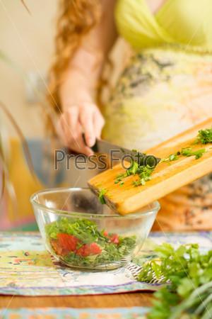 Руки режут свежий лук, укроп, петрушку. Концепция здорового питания