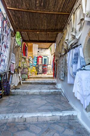 Фотография на тему Традиционный текстиль на рынке, красочные ткани, сувениры ручной работы, Греция