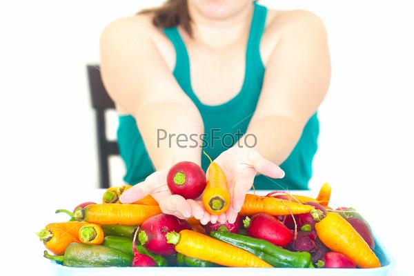 Молодая женщина держит в руке редис и куча овощей на столе