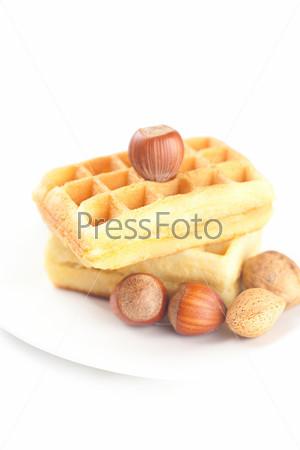 Бельгийские вафли и орехи на тарелке, изолированные на белом фоне