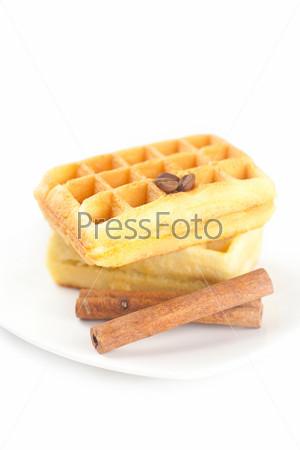Бельгийские вафли, кофейные зерна и корица на тарелке, изолированные на белом