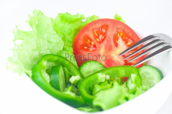 Фотография на тему Вилка, листья салата, помидор, огурец и перец в миске, изолированные на белом