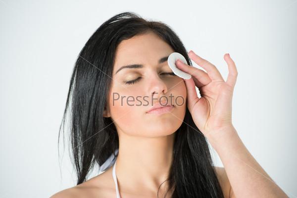 Женщина очищает лицо ватным тампоном
