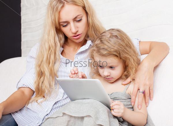 Мать и дочь с планшета на диване
