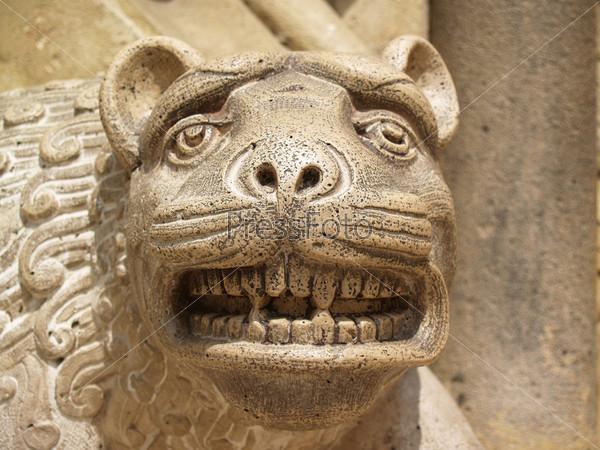 Лицо старого каменного мистического животного в парке