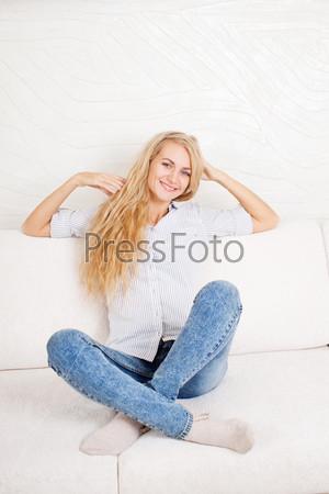 Счастливая молодая женщина на диване