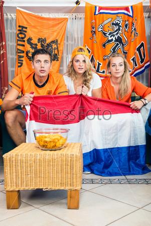 Любопытные футбольные болельщики смотрят матч дома
