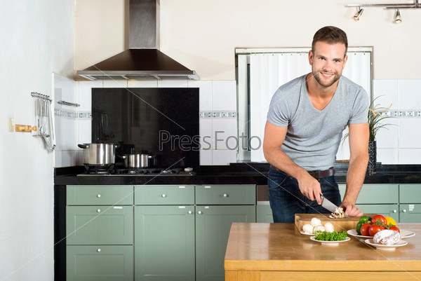 Мужчина режет овощи на кухне