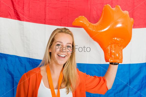 Спортивный болельщик с надувной оранжевой  рукой на фоне голландского флага
