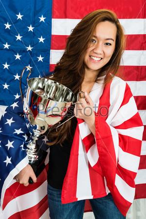 Спортсменка с трофеем на фоне флага Северной Америки