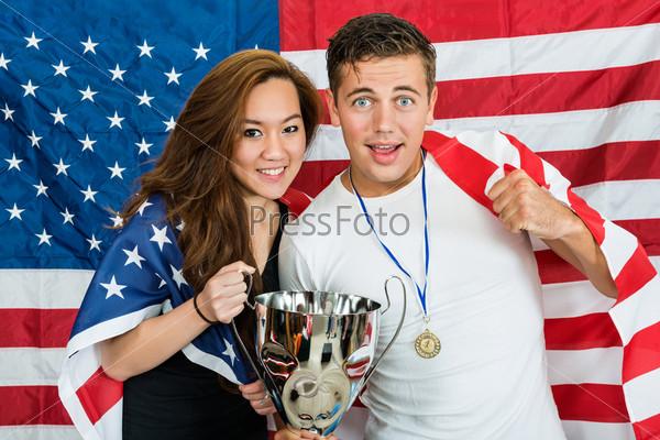 Спортсмены с трофеем и медалью стоят на фоне флага Северной Америки