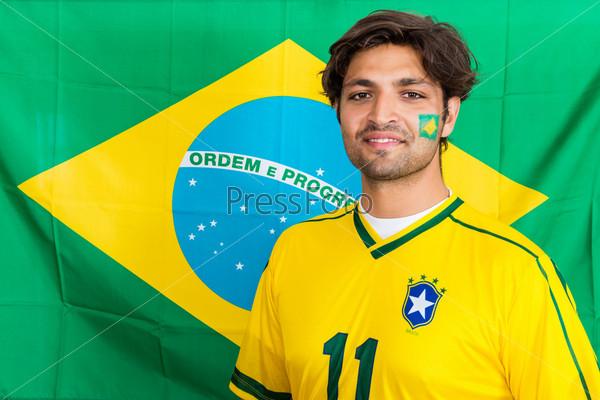 Бразильский фанат на фоне бразильского флага