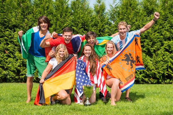 Международные спортсмены с различными национальными флагами в парке