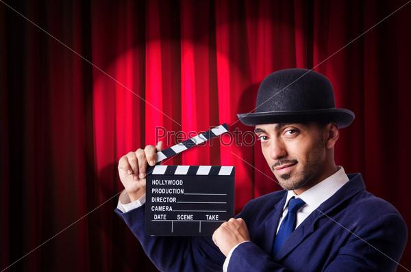 Мужчина с кинохлопушкой на фоне занавеса