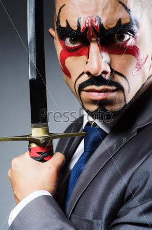 Мужчина с раскрашенным лицом и мечом