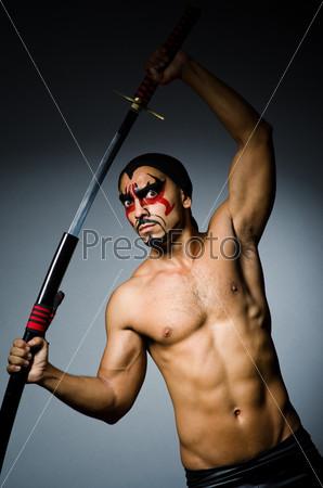 Фотография на тему Мужчина с мечом и раскрашенным лицом