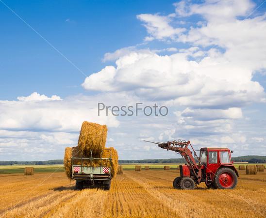 Трактор, перевозящий солому
