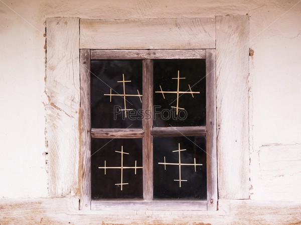 Окно с крестами в старом доме в деревне