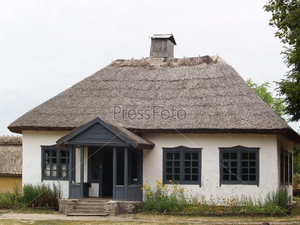Старая школа в маленькой деревне, сделанная из глины, с соломенной крышей