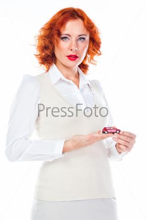 Молодая и красивая женщина с игрушечной машиной в руках