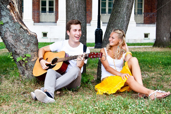 Фотография на тему Молодой мужчина играет на гитаре в парке красивой женщине