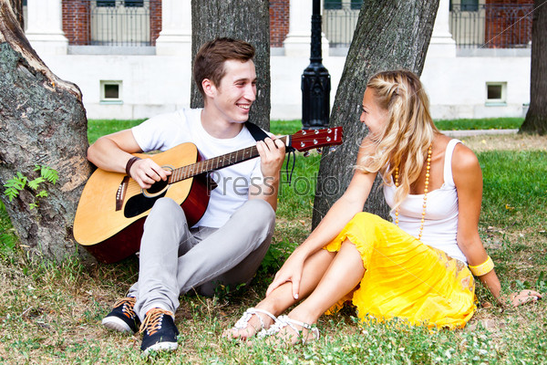 Молодой мужчина играет на гитаре в парке красивой женщине