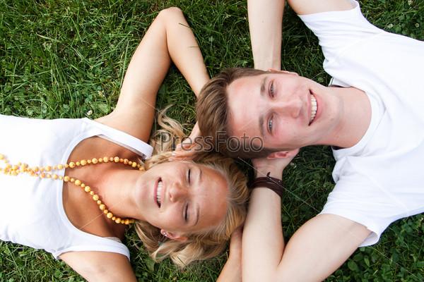Фотография на тему Молодые мужчина и женщина лежат на траве головой к голове