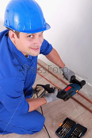 Фотография на тему Водопроводчик бурит стену