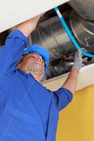 Сантехник держит синюю гибкую трубу под  воздуховодом