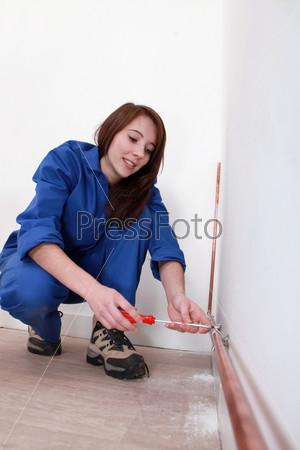 Рабочий фиксирует медную трубу к стене