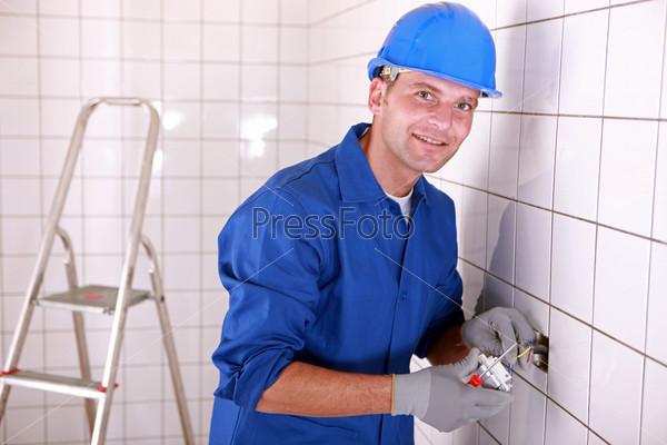 Фотография на тему Электрика монтирует переключатель в комнате