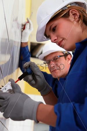 Жлектрик устанавливает электрическую розетку