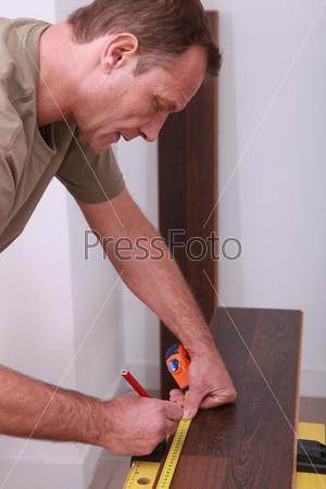 Рабочий измеряет паркетную доску