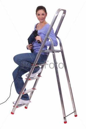 Фотография на тему Женщина с дрелью, сидящая на лестнице