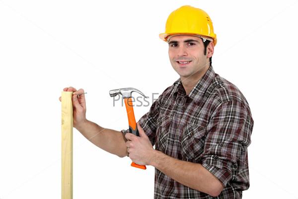 Плотник забивает гвоздь в доску