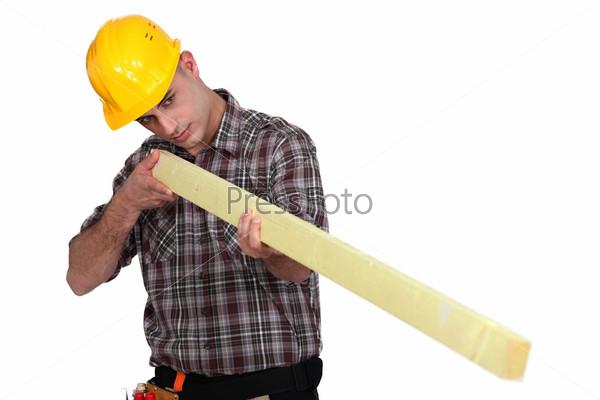 Мужчина держит деревянный брус