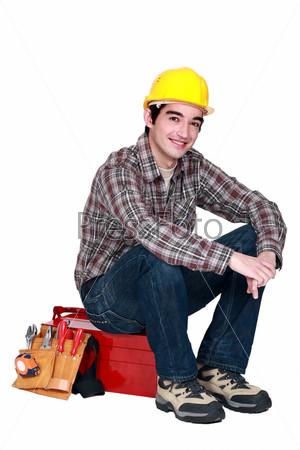 Рабочий сидит на коробке инструментов