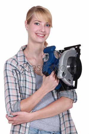 Улыбающаяся молодая женщина, держащая дисковую пилу