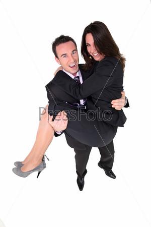Бизнесмен несет на руках партнера