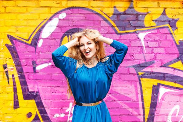 Молодая привлекательная блондинка возле стены с граффити