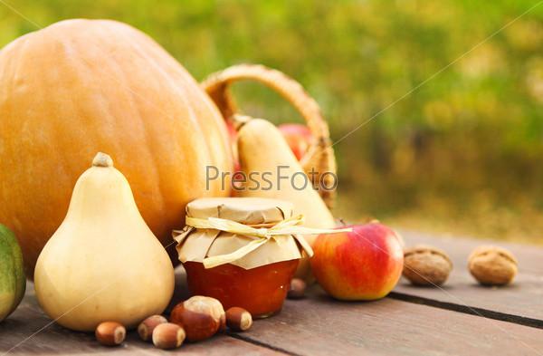 Тыквы, варенье, орехи и корзина с яблоками