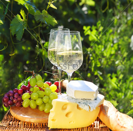 Различные виды сыра, хлеба, винограда и два стакана белого вина