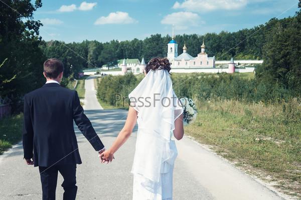 Фотография на тему Пара молодоженов идет по дороге, взявшись за руки