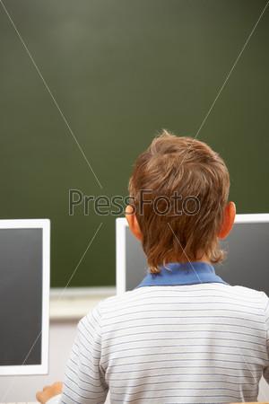 Фотография на тему Школьник сидит за компьютером спиной к камере