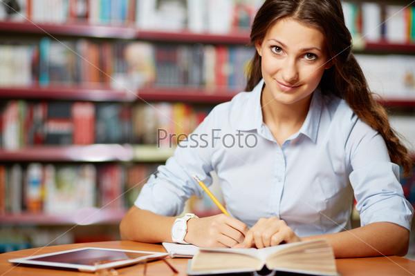 Девушка делает заметки в библиотеке