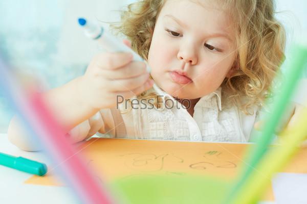 Девочка увлеченно рисует