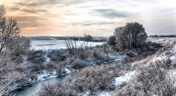 Фотография на тему Зимний пейзаж с рекой и редкими деревьями
