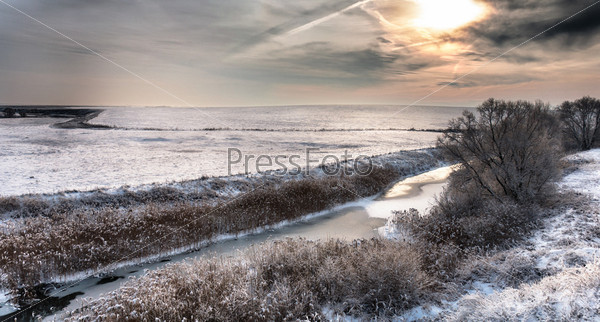 Зимний пейзаж с рекой и редкими деревьями