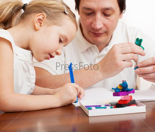 Девочка и папа делают глиняные игрушки
